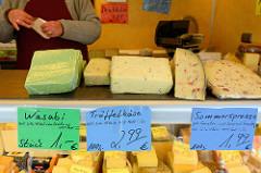 Wochenmarkt auf dem Marktplatz in Hamburg Rothenburgsort; Marktstand mit Käse, z.  B.  Trüffelkäse, Wasabi und eine Käsesorte mit dem Namen Sommersprosse.
