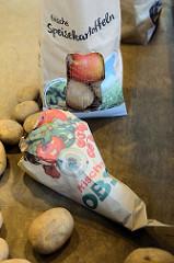 Wochenmarkt auf dem Marktplatz in Hamburg Rothenburgsort; Marktstand mit Obst und Gemüse, Papiertüten mit der Aufschrift frische Speisekartoffeln und frisches Obst.