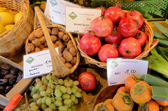 Obst und Gemüsestand auf dem Wochenmarkt   im Hamburger Stadtteil Ottensen / Spitzenplatz; Körbe mit Granatäpfeln, Walnüssen und Kaki.