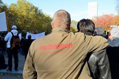 Aktionstag der überparteilichen Sammlungsbewegung Aufstehen - Sammelplatz der Demonstration mit dem Motto Würde statt Waffen auf dem Platz der Republik in Hamburg Altona. Ein Demonstrant trägt eine Jacke mit der Aufschrift Aufstehen die Sammlungsbewe