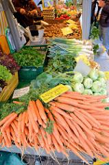 Marktstand mit Gemüse auf dem Wochenmarkt am Moorhof im Hamburger Stadtteil Poppenbüttel; im Vordergrund liegen frische Möhren und Kohlrabi.