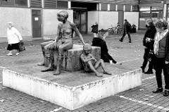 Kunst im öffentlichen Raum; Bronzeskulptur zwei Frauen mit Kind, Steinblock   auf dem Parkplatz Bei den Höfen in Hamburg Jenfeld.