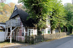 Alte Fachwerkkate mit Reetdach und Holzzaun Lindenbäume stehen vor dem historischen Gebäude, das im 18. Jahrhundert errichtet wurde. Als Kulturdenkmal Hamburgs steht das Wohnhaus unter Denkmalschutz.