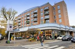 Mehrstöckiges Wohnhaus an der Wedeler Landstraße in Hamburg Rissen, im Erdgeschoss befinden sich Geschäfte.