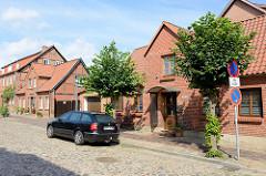 Kopfsteinpflaster in der Straße Bollenberg in Boizenburg/Elbe; Doppelhäuser mit Mittelrisalit - Fachwerk mit Backsteinfassade, teilweise neu verklinkert.