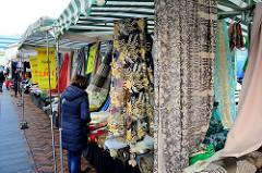 Marktstand mit Stoffen auf dem Wochenmarkt in der Großen Bergstraße, Stadtteil Hamburg Altona / Altstadt;   Stoffbahnen mit unterschiedlichen Mustern hängen vom Dach des Standes.