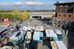 Blick von oben auf die Marktstände vom Wochenmarkt Neuallermöhe auf dem Fleetplatz. Im Hintergrund die S-Bahn Haltestelle von Allermöhe.