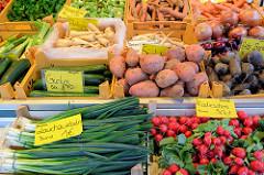 Marktstand mit Gemüse auf dem Wochenmarkt am Moorhof im Hamburger Stadtteil Poppenbüttel; Lauchzwiebeln, Radieschen, Gurken, Süßkartoffeln, Pastinaken und Rote Beete liegen zum Verkauf bereit.
