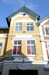 Wohnhaus  / Geschäftshaus  in der Straße Steendiek im Hamburger Stadtteil Finkenwerder; gelbe Ziegelfassade Jugendstil Stuckrelief mit der Inschrift erbaut A. D. 1902