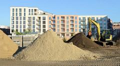 Baustelle mit großen Sandhaufen  auf dem Gelände des ehemaligen Güterbahnhofs Hamburg Altona - im Hintergrund neu gebaute Wohngebäude.