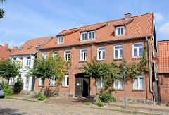 Baudenkmal am Bollenberg in Boizenburg/Elbe; in der Mitte des historischen Doppelhauses befindet sich eine Toreinfahrt mit Holztür. Die Straße ist mit Kopfsteinpflaster versehen.