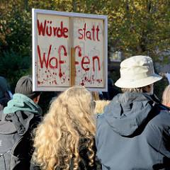"""Aktionstag der überparteilichen Sammlungsbewegung Aufstehen - Sammelplatz der Demonstration mit dem Motto Würde statt Waffen auf dem Platz der Republik in Hamburg Altona. Protestschild mit der Aufschrift """"Würde statt Waffen""""."""