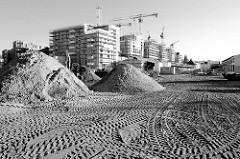Baustelle mit großen Sandhaufen und Reifenspuren auf dem Gelände des ehemaligen Güterbahnhofs Hamburg Altona - im Hintergrund entstehen Wohngebäude.