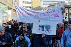 Aktionstag der überparteilichen Sammlungsbewegung Aufstehen -  Demonstration mit dem Motto Würde statt Waffen in der Ottenser Hauptstraße von Hamburg Altona. Transparent mit der Aufschrift  Die Waffen liefern die reichen, die Armen liefern die Leiche