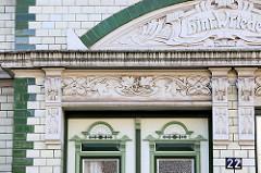 Detail / Fassadendekor eines  Jugendstil-Gebäudes mit weiß glasierten Kacheln und grünen Bändern im Auedeich von Hamburg Finkenwerder; die Fassade ist mit aufwändiger Jugendstilornamentik und dem Schriftzug Hinr. Wriede  verziert.