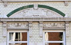 Detail / Fassadendekor eines  Jugendstil-Gebäudes mit weiß glasierten Kacheln und grünen Bändern im Auedeich von Hamburg Finkenwerder; die Fassade ist mit aufwändiger Jugendstilornamentik und dem Schriftzug Bäckerei verziert.