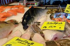 Fischstand mit frischem Fisch auf dem Wochenmarkt am Quarree im Hamburger Stadtteil Wandsbek; ein ganzer Lachs liegt auf Eis, Schellfisch und Heilbutt werden angeboten.