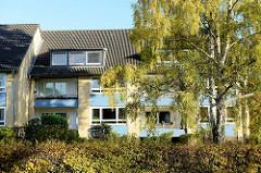 Architektur der 1960iger Jahre, Wohnhäuser mit gelber Ziegelfassade und blauen Feldern in der Straße bei den Höfen in Hamburg Jenfeld.