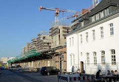 Historische Lagerhäuser mit Laderampe  auf dem Gelände des ehemaligen Güterbahnhofs Hamburg Altona Nord, dahinter die Baustelle von Neubauwohnungen und Baukräne.