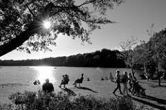 Sonnentag an der Promenade der   Außenmühle im Stadtpark von Hamburg Harburg; Spaziergänger schlendern um den kleinen See andere sitzen auf Einzelstühlen in der Sonne. Gegenlichtsaufnahme, die tief stehende Sonne strahlt durch die Blätter eines Baum