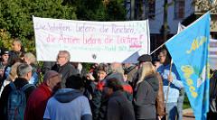 Aktionstag der überparteilichen Sammlungsbewegung Aufstehen - Sammelplatz der Demonstration mit dem Motto Würde statt Waffen auf dem Platz der Republik in Hamburg Altona.  Transparent mit der Aufschrift Die Waffen liefern die reichen, die Armen liefe