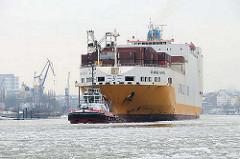 Hamburger Hafenbilder vom Winter - RoRo Schiff mit Schlepper im Elbeis.