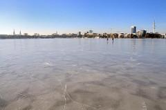 Hamburgs Winter - sonniges Winterwetter, blauer Himmel über der zugefrorenen Aussenalster.
