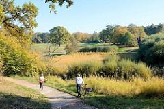 Fußweg am Ufer der Flottbeck im Naturschutzgebiet Flottbeck-Tal im Jensichpark von Hamburg-Othmarschen; Bäume und Gräser zeigen ihre herbstliche Färbung.
