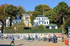 Mehrstöckige Wohnhäuser am Elbufer in Hamburg Ottensen / Övelgönne; Spaziergängerinnen am Sandstrand.