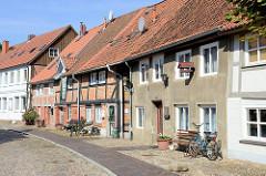 Denkmalgeschützte Wohnhäuser in der Großen Wallstraße von Boizenburg/Elbe; die Straße ist mit Kopfstein-Pflaster gepflastert.