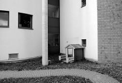 Kleines Holz-Kinderhaus  am modernen Gebäude der Kita Fleet Kinder im Hamburger Stadtteil Neuallermöhe.