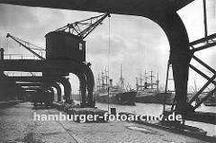 Alte Hamburgbilder - Fotos aus dem Hamburger Hafen, Krananlagen auf dem Hafenkai. Kräne am Amerikakai im Segelschiffhafen des Hamburger Hafens - ein Güterwagen der Hafenbahn steht auf den Gleisen am Kai und wird beladen.