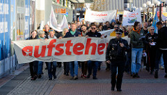 """Aktionstag der überparteilichen Sammlungsbewegung Aufstehen - r Demonstration mit dem Motto Würde statt Waffen in der Ottenser Hauptstraße von Hamburg Altona. Transpart mit roter Aufschrift """"aufstehen""""."""