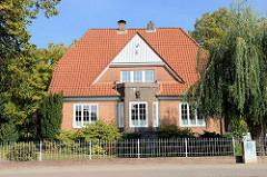 Wohnhaus mit Mansarde und Backsteinerker sowie Keramikbild in der Fassade, Hauptstraße in Trittau.