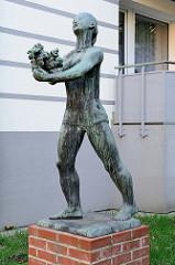 Bronzeskulptur,  schreitende  Frau mit Blumenstrauß in Hamburg-Harburg, Bildhauer Karl August Ohrt.