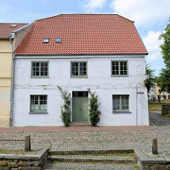 Historisches Wohnhaus, Fachwerkgebäude mit weißer Fassade und Rosenstöcke am Eingang in der Straße frische Grube in Wismar; das Gebäude steht als herausragendes Baudenkmal der Hansestadt unter Denkmalschutz. Im Vordergrund ein Treppenabgang zum Mühle