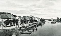 Historische Ansicht vom Ufer der Alten Oder in der Stadt Oderberg; Holzkähne sind an Land gezogen, zwei Binnenschiffe fahren mit Segelunterstützung oderabwärts.