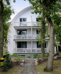 Villa mit Ferienwohnungen mit weit heruntergezogenem Tonnendach am Strandweg im Ostseebad Boltenhagen.