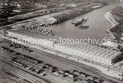 Luftfoto vom Windhukkai des Süd-West-Hafens,  dem Lagerschuppen 59  mit den Tonnengewölben am Veddeler 9amm und den Gleisanlagen des Güterbahnhofs Hamburg Süd. Ein Frachter liegt an den Dalben in der Mitte des Hafenbeckens.