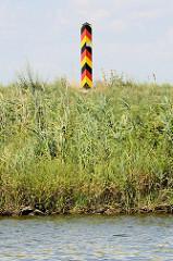 Ufer von der Hohensaaten-Friedrichsthaler Wasserstraße, die durch den  Nationalpark Unteres Odertal führt;  ein Grenzpfahl in den deutschen Farben schwarz-rot-gold steht am Kanalufer.