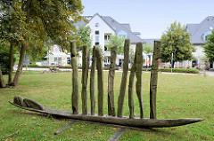 """Eichenholzskulptur """"Menschen im Sturm"""" vor der Kirche auf der Paulshöhe in Boltenhagen."""