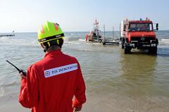Ein Unimog U 2150 L der Deutschen Gesellschaft zur Rettung Schiffbrüchiger (DGzRS) fährt rückwärts  den Trailer ins Wasser, um das Seenotrettungsboot Zander aufzunehmen.