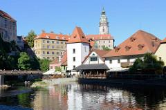 Blick über die Moldau zur Fußgängerbrücke und dem Schloss von Krumau / Český Krumlov.