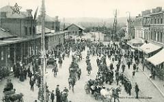 Historische Ansicht beim Bahnhof in Lüttich / Liège.  Militär reitet über den Bahnhofsplatz, Pferdedroschken mit Passagieren fahren durch die Menschenmenge - im Hintergrund stehen Güterwaggons auf dem Gleis.