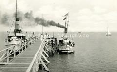 Altes Foto der Seebrücke in Boltenhagen mit Ausflugsschiffen; rechts liegt der Kutter Insel Poel unter Dampf, links das Fahrgastschiff Seemöwe.