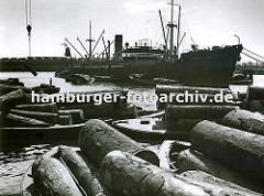 Ein Frachtschiff liegt im Südwesthafen auf Reede; seine Ladung, die in Säcken verpackt ist wird gelöscht und mit bordeigenem Ladegeschirr auf Schuten verladen - im Hintergrund die Lagergebäude am Windhukkai.