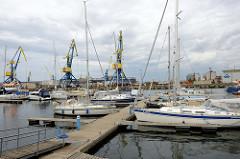 Sportboote - Segelboote / Motorboote am Steg  vom Wasserwandererrastplatz Brunkowkai in der Hansestadt Wismar; im Hintergrund  Hafenkräne.
