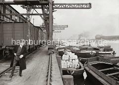 Schuten liegen am Afrikakai des Hamburger Südwesthafens - einige der Lastkähne sind leer, während ein anderer mit Holzkisten hoch beladen ist. Unter den Halbportalkranen steht ein Güterzug; im Hintergrund dampft ein Schlepper in dem Hafenbecken.