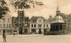Historisches Motiv vom Marktplatz in der Hansestadt Wismar; im Hintergrund unter anderem das älteste Bürgerhaus Wismars, das Gästehaus alter Schwede. Das Gebäude wurde um 1380 im späten backsteingotischen Stil  errichtet. Rechts der Brunnen der
