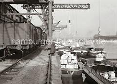 Die Schuten liegen dicht gedrängt am Afrikakai des Südwesthafens - die Lastkähne haben keinen eigenen Antrieb sondern werden mit Schleppern über das Wasser des Hamburger Hafens bewegt. An den Kranhaken der Kaikrane hängen Kisten.